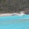 Boat broadside on beach is a water taxi that got on the wrong side of the surf.