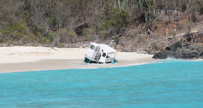 this poor water taxi got tangled up in the surf and landed on the beach. The tug arrived planning to haul it off of the beach once they dug it out...by hand...in order to free it up.