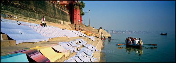 Boat of local pilgrims passing drying laundry. Varanasi, India.