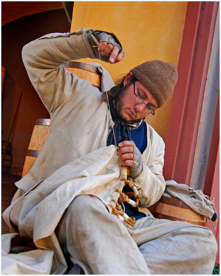 CJ, a maritime reenactor, sews his own clothes in the doorway to the Powder Magazine, one of the oldest buildings in Charleston, SC.