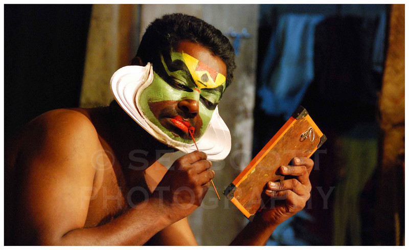 A Kathakali performer applies his elaborate makeup in Cochin, India.