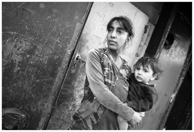 A Gypsy mother and child stand before the door to their small, single room apartment.  Presov, Slovakia.