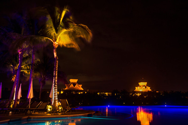 The roofs of the Grand Mayan resort complement the pool and palm trees.