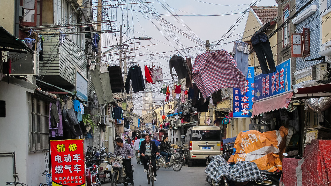 The classic Shanghai shot of clothes hanging out to dry in the middle of a crowded street.