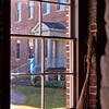 Woman acting as a maid to welcome visitors. Tryon Palace New Bern North Carolina seen through the stable window