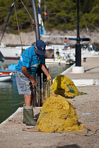 Fisherman in Assos Fisherman tidying his nets
