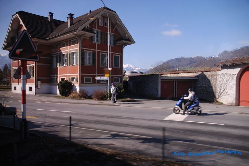 """Another interesting """"from the train"""" photo featuring transportation. You can see the Alps behind this building. We are in the middle of them at a respectable altitude. I think the over sized roof architecture is to accommodate the snow."""