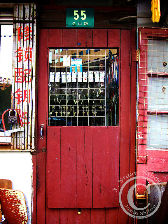 """Chinese Locksmith No. 55  From the ship's dock I could see a fabulous iron bridge that called out to be photographed.  I told myself that I would capture an interesting image of the bridge, but on my venture across Shanghai's waterfront I came across a more interesting subject, a locksmith.  Something about this storefront held, and still holds, my attention.  The vibrant red door, keys hanging in the window, green address panel, folded window bars, and tiny lock used to keep the lower door panel closed brought so much character to the facade.    The usual sights are important for visitors to <i>check off the list</i>, but often times other important sights are lost in the shadows of tourist attractions.  In my experience, these <i>lost sights</i> usually exude more character and tell a different story than most tourists """"hear.""""  Next time you are in a foreign land, or a city in your own backyard, remember there is more to an area than the local hotspot.  Reach outside of your comfort zone and explore; you might surprise yourself!  March 20, 2010"""