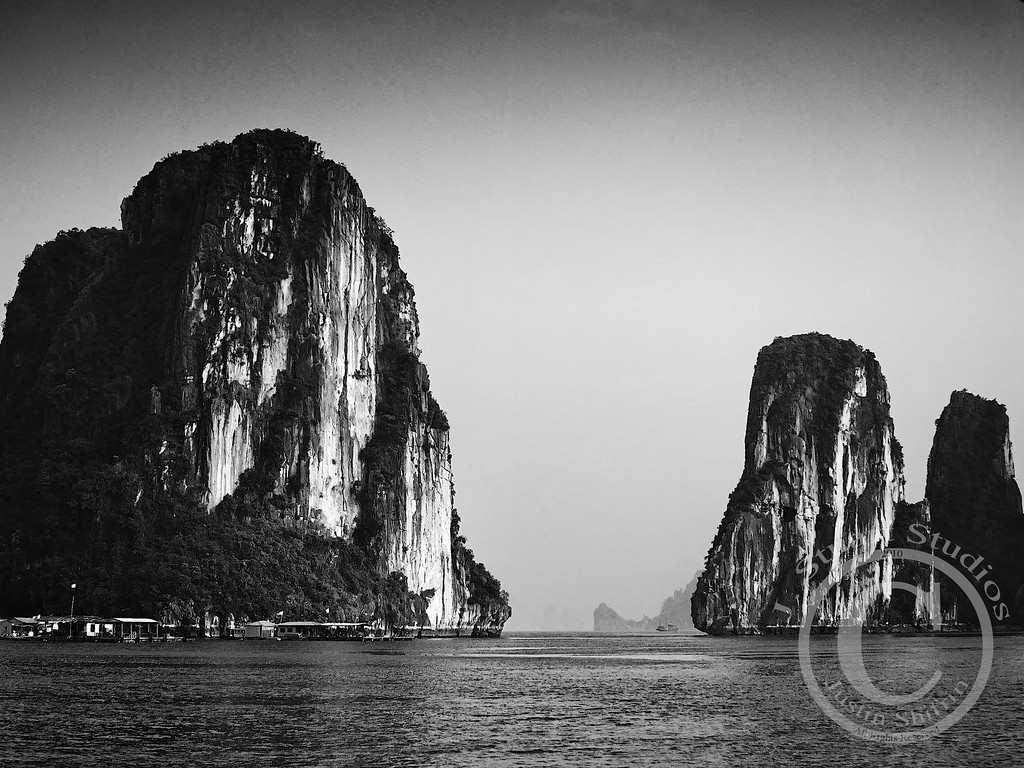Gateway Cliffs  Thick humid air fogged up the lens as our ship ventured through the straits of Ha Long Bay.  The image above was captured as we passed through a natural gate with sheer cliffs on either side.  This landscape was extraordinary for a foreigner.  Imagine the difficulties of living on the waterline of the cliffs.    Notice the structures in the bottom left of this photograph.  Numerous businesses operate throughout the bay, including a bank.  It is easy to take necessities, and luxuries, for granted in the United States.  Groceries are simple to obtain at the store, fresh water connections are in most homes, and electricity is plentiful.  Most people give little thought to the supply chain and logistics of the services we consume.  However, the supply chain on Ha Long Bay must be intricate for goods unobtainable from the sea beneath.  I cannot imagine the complexities of procuring every foodstuff, generating electricity, and living without plumbing.  This is one of <i>many</i> reasons why I feel extremely lucky!  February 27, 2010