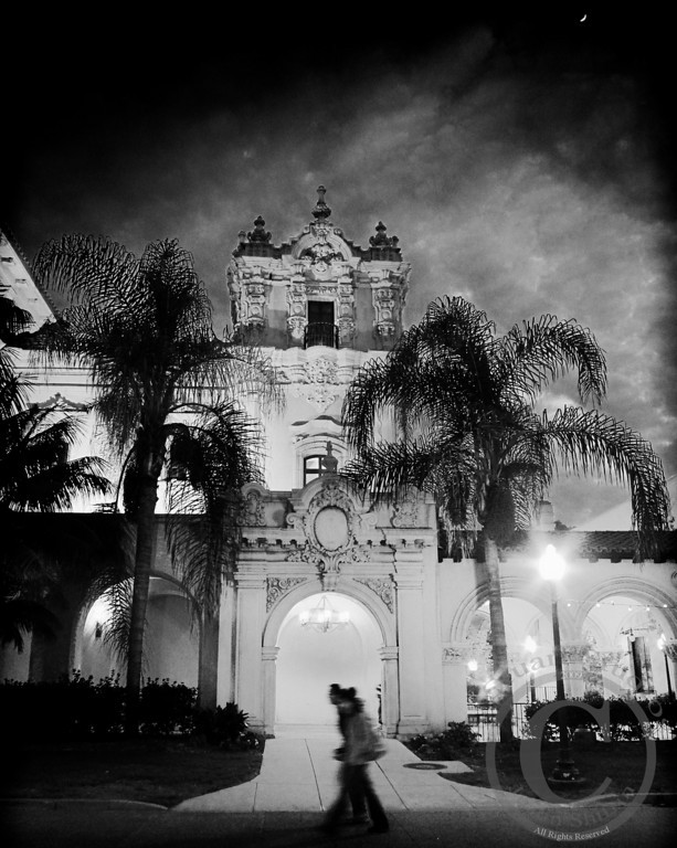 Balboa Evening Stroll<br /> <br /> On a warm evening the summer air began to cool as evening fell upon San Diego's Balboa Park.  This couple will forever be locked in my memory of this lovely architectural sight.  The couple's affection for each other was apparent to anyone watching the two lovebirds stroll through the park.<br /> <br /> <br /> January 27, 2010