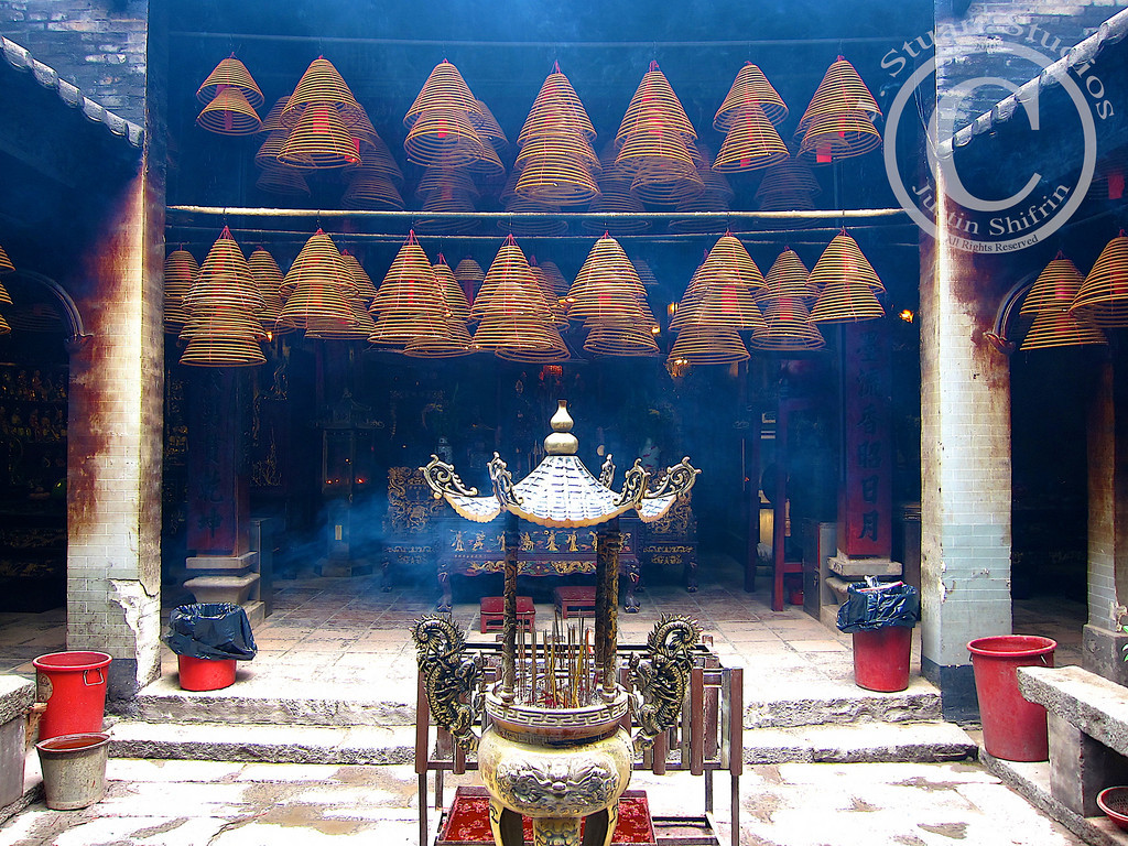 Smoke-filled...Monastery<br /> <br /> While in Hong Kong we did a full-day tour of the islands and stumbled across this smoke-filled monastery.  From the image above it is hard to see past the numerous hanging incense cones and the grimy cinderblock walls covered in soot from incense.  However, deep in the shadows of the altar the gilt furniture and dark woods accentuate the room's connection to a higher power.  <br /> <br /> I was told that some of the cones of incense can burn for two weeks.  If you look closely you might be able to find red prayers hanging within the incense.<br /> <br /> March 3, 2010