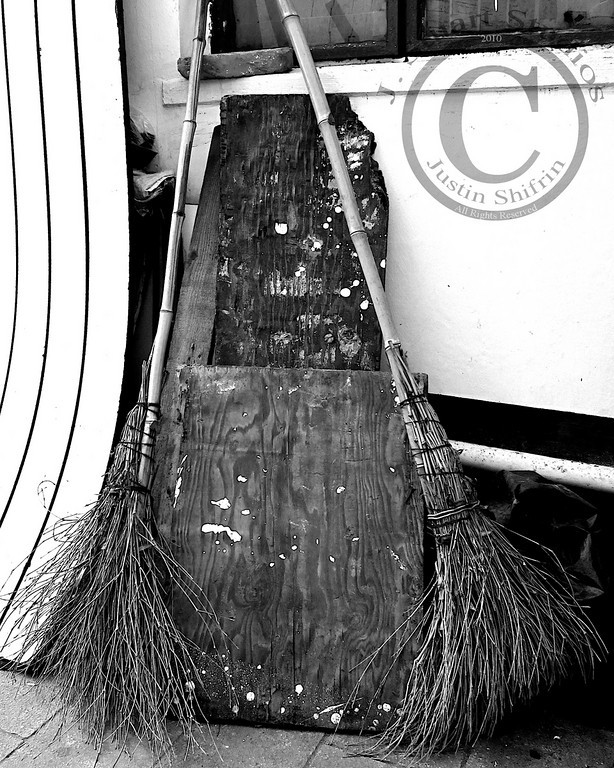 Broom Scape  While traveling through China I came across an extreme irony, brooms.  Take a look at the broom(s) you have in your cupboard.  Many of us have multiple sweeping implements for different tasks.  I have a broom for sweeping large areas, another for smaller areas, and yet one more handheld broom to gather crumbs and little pockets of debris.  In fact, I have a micro broom, actually a paintbrush, used to remove dust that gathers on camera equipment.  Each of the brooms that I own were made in China.  It is through this lens that my <i>broom</i> intrigue began.  With that intro behind us, lets get ironic.  Throughout Chinese cities I witnessed government workers, construction personnel, and other citizens using presumably homemade straw/stick brooms.  Aren't the majority of brooms in the United States made in China?  On one occasion I passed by a massive construction site outside of Shanghai (the car was traveling too rapidly for me to capture the best example of workers utilizing the type of broom pictured above).  Numerous construction workers were erecting a large complex and parts of the sidewalk and roadway were torn up.  Three female construction workers were tasked with removing dust and other particulate with straw brooms.  The job looked daunting due to the winds created by passing motor vehicles and the sheer amount of debris strewn about.  Why were these workers using homemade brooms rather than those manufactured for export in China?  I bet cost is an issue, but the situation did strike me as a bit odd.  The workers were clad in vibrant blue jumpsuits fit for any Western factory worker, but the brooms were homemade, not the dense synthetic brooms sold at your local mega-mart.  Strange.  Venturing to the very place where many of our goods are fabricated presented an opportunity to view local life in the context of a manufacturing hub.  Much of life in urban China seemed to mirror the United States.  Underlying customs differ from the West, as is t