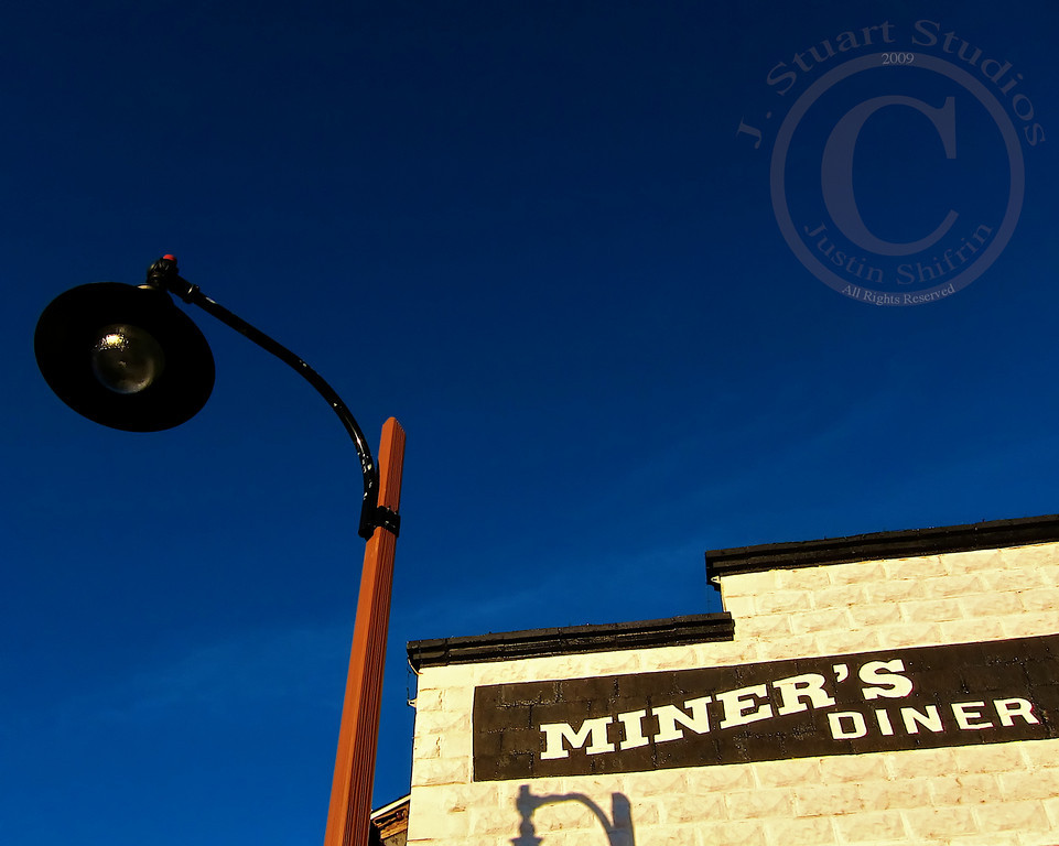 Miner's Diner<br /> <br /> Wispy clouds dusted the deep azure sky outside of the big city.  At elevation the air was crisp, cleansing, and cool.  The stark contrast between the brightly lit stonework and the vibrant sky was enough to bring the camera to eye-level and expose a frame.<br /> <br /> <br /> January 16, 2010