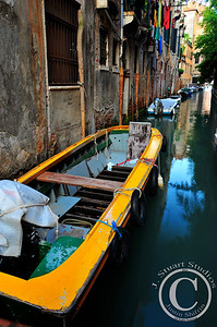 Wall Tied  A simple anonymous canal in Venice, Italy highlights the everyday lives of those living out in the lagoon.  The bright yellow vessel directs one's attention down the line of other boats moored to the aging building and to the clothes hanging out to dry above the waterway.  Ago vita vos somnium (live the life you dream)