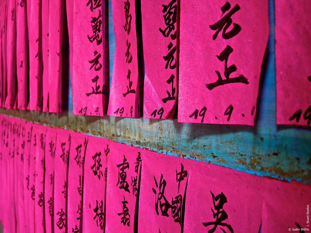 Prayer Paper (Canon S90)<br /> <br /> Many of the temples that once stood lonely on the Chinese landscape have now been incorporated into cities.  At one such smoke-filled temple, pink prayer papers were tacked to the wall.  These intriguing papers stood out on the rusted teal-painted metal wall.  In a far corner, baby turtles splashed in a trough near the altar.  The incense and water sounds masked the bustling city's noise and brought serenity to the worshipers.    <br /> <br /> The shallow depth of field used in this composition helped to capture the magnitude of the pink prayer papers affixed to the temple's wall.  Row after row, column after column.<br /> <br /> December 28, 2009
