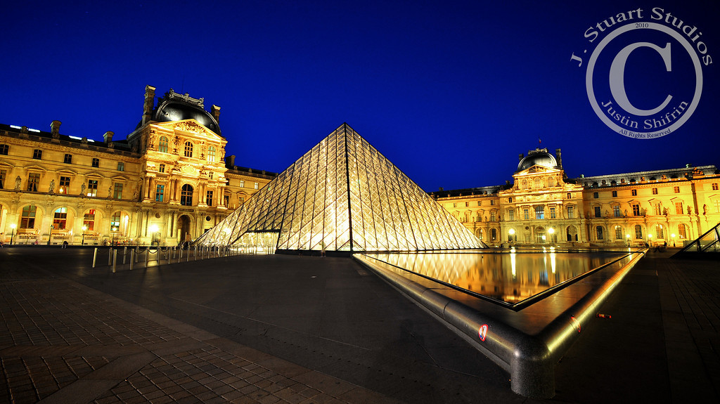 """Louvre, Pyramid, & Water<br /> <br /> Sometimes photographers get lucky and other times we work hard to get the shot.  This photograph was a combination of the two.  I was out shooting with my Nikon when other people were eating dinner and enjoying Paris' nightlife.  Hanging around the Louvre at the """"right"""" time was key.  I was lucky because virtually all the Parisians and tourists cleared out of the Louvre's courtyard.  The resulting image is near absent of people, save for a few shadows and blurry figures in the distance.  Diligence put me in the right place to take advantage of my surroundings, and what wonderful surroundings they were.<br /> <br /> Ago vita vos somnium (live the life you dream)"""