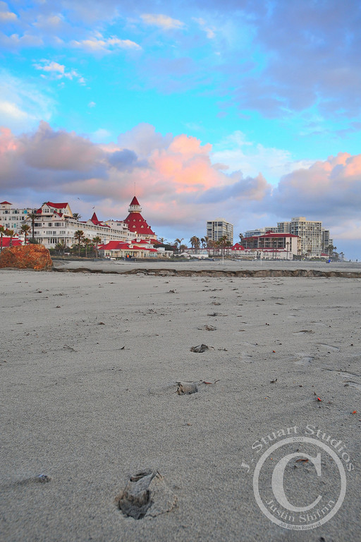 Footprints to The Del<br /> <br /> When I set out, the skies were filled with gray gloom and rain was not in the cards.  Once I was halfway to my destination, the clouds opened up and released pent-up moisture.  Down at Coronado, California I waited out the storm.  Smooth sandy beaches resulted from the morning's precipitation and set up the above photograph.  The wait was worth the time!<br /> <br /> As the sun set on the horizon, my polarizer helped bring out detail in the clouds above Hotel Del Coronado and enhanced the teal sky.  The curved footprint trail leads the eye to the conical roof of The Del.  I thank the beach-goer who left their footprints in the sand!