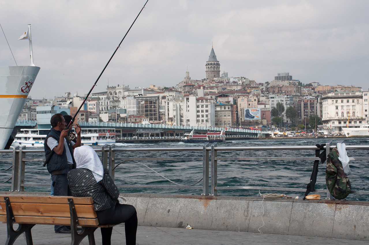 Looking across the Golden Horn, eating our fish sandwiches,  watching a fisherman.