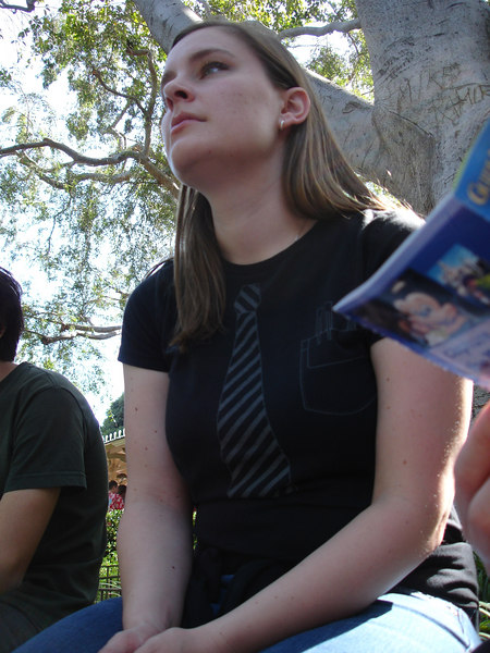 Caitlin (with the rest of us) escapes the heat in the shade of a New Orleans Square tree.