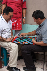 These guys are taxi drivers waiting for a fare playing checkers in the park. Notice the gatorade bottle caps that they are using for checkers! They thought that it was very funny that I was taking their photo, but they were very nice about it. San Salvador, El Salvador.