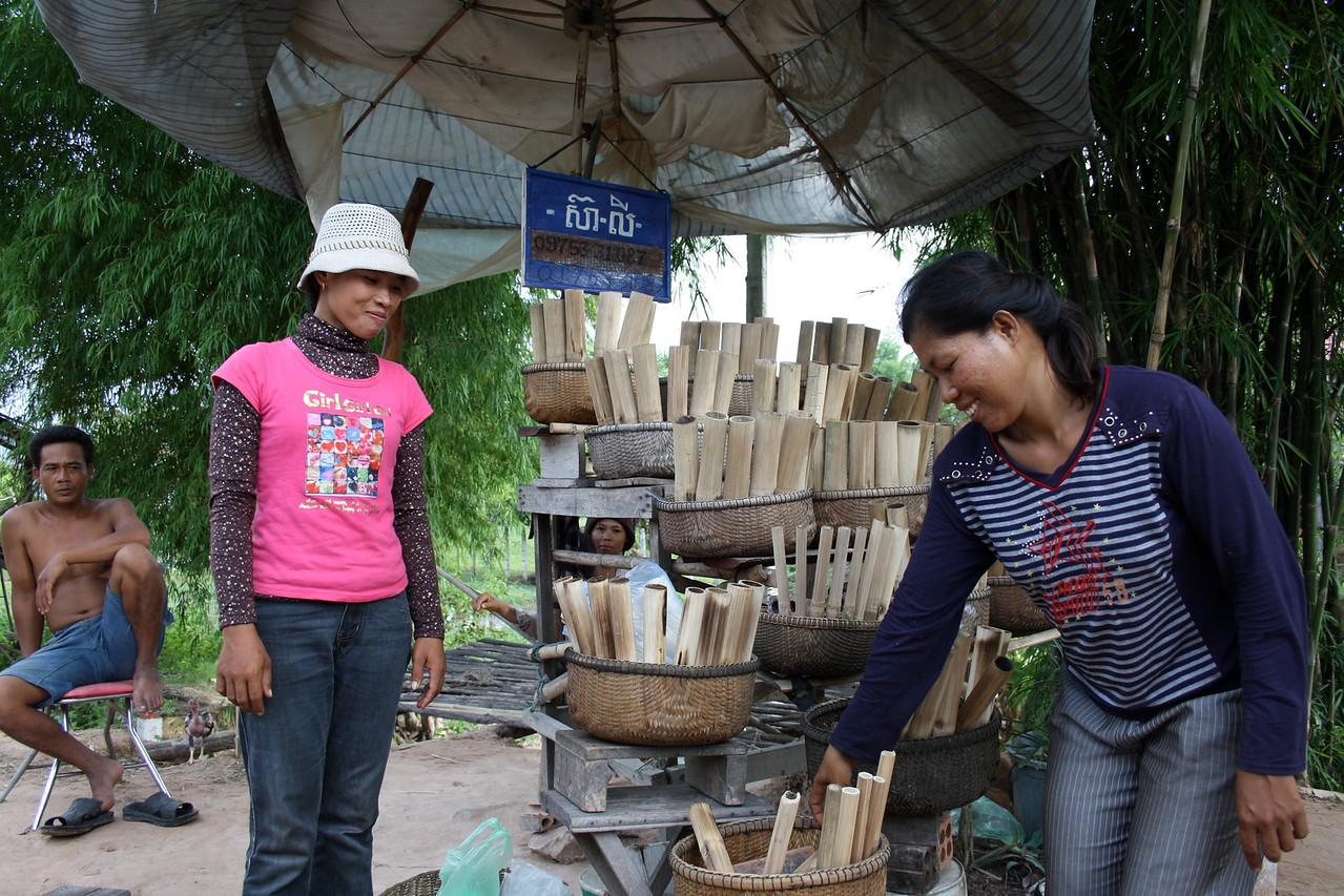 Along the road we passed by two Khmer women baking and selling krorlarn. They displayed their products on wooden stands for the passing motorists.