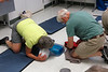 Cathy and John apply CPR and prepare the automatic external defibrillator (AED) for service.