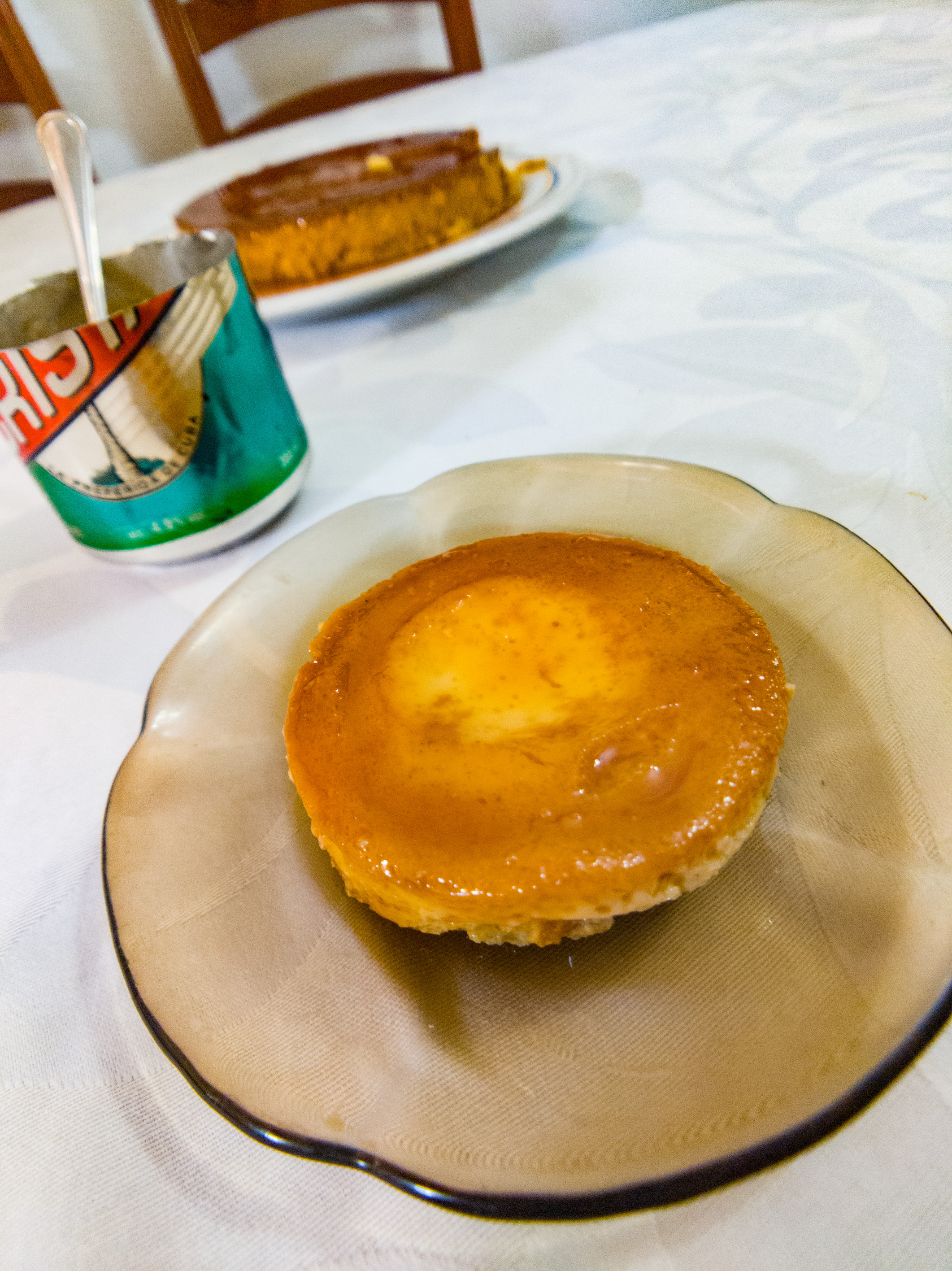 Cuban flan is often cooked in a beer can or soda can. On the table with the can in the background.
