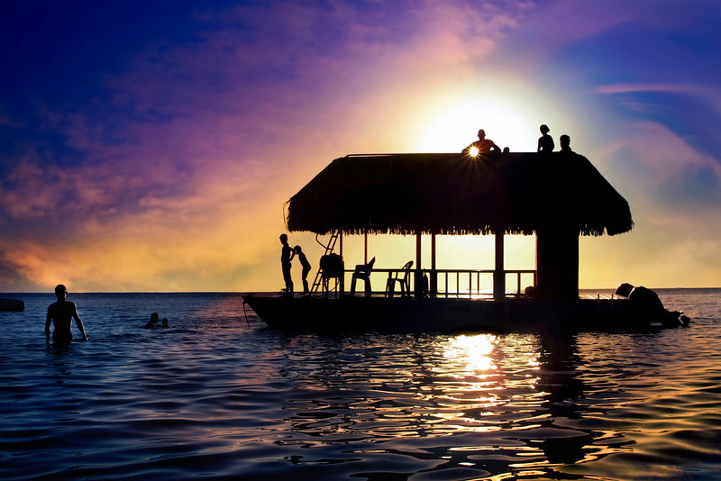 Sunset image with silhouette of boat and children playing.  Photo by Christian Wilkinson.