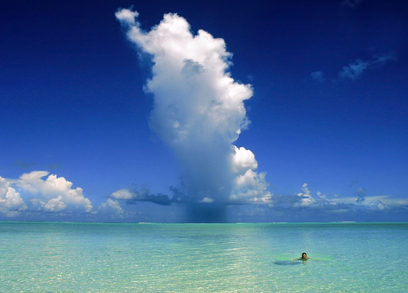 Rain cloud over calm, clear waters at the Pacific Island of Bora Bora.  Photo by Christian Wilkinson.