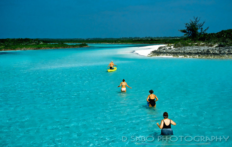"""Tropical Conga Line""   Vacationers take a break from diving and venture into the lagoon waters in and around the Exuma Islands, Bahamas."