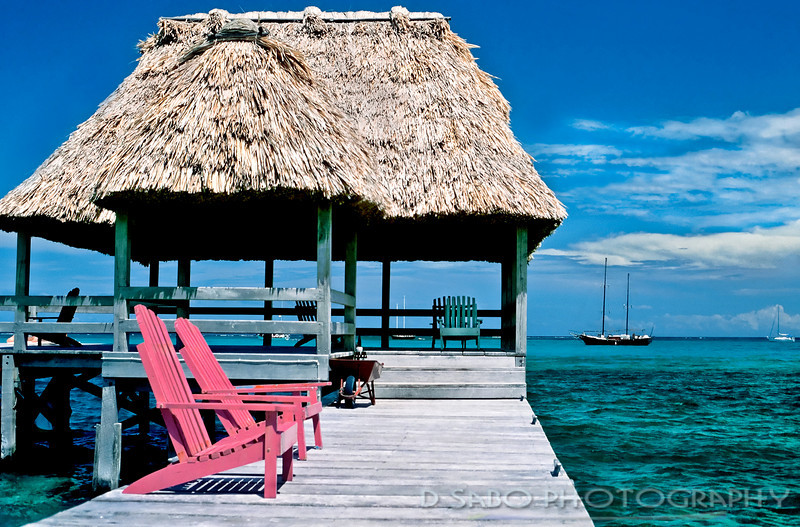 """Ambergris Pink""  Thatched dockside pink chairs at a resort on Ambergris Caye, Belize circa 1990."
