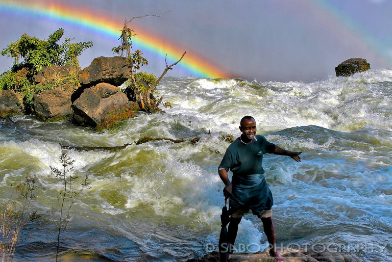 """Singing on the Falls""   ill Advised tourist strolls along the slippery rocks of the Victoria Falls head waters.  The falls dropoff is right at the boulder rocks edge. Photo taken from Zambia side of the falls."
