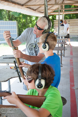 Grandpa is teaching that boy how to load the gun.
