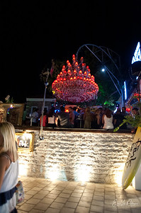 This huge chandelier is hung over an outdoor bar.