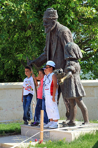 Turkish children pose with the statue to the last surviving Turkish soldier who fought the ANZACs.  Turkish Memorial along the ridge between Lone Pine and Chunuk Bair.