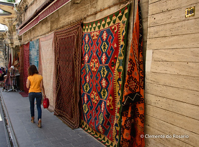 File Ref: 2013-06-04-Istanbul  277 Young girl walking in a side street drapped with turkish carpets for sale. Istanbul