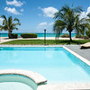 Beach beyond resort pool and gardens, Caribbean white sand, turquoise sea, and blue sky. Providenciales, Turks & Caicos.