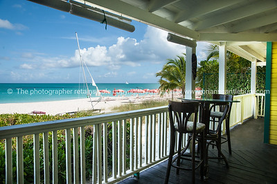 Beach from cafe patio, Caribbean white sand, turquoise sea, and blue sky. Providenciales, Turks & Caicos. Prints & downloads.
