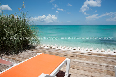 Beach beyond deck and lounger, Caribbean white sand, turquoise sea, and blue sky. Providenciales, Turks & Caicos.