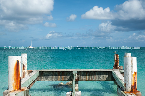 Remains of jetty on beach, Caribbean white sand, turquoise sea, and blue sky. Providenciales, Turks & Caicos.<br /> Prints & downloads.