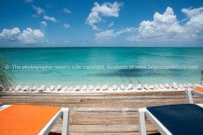 Beach beyond deck with loungers, Caribbean white sand, turquoise sea, and blue sky. Providenciales, Turks & Caicos.