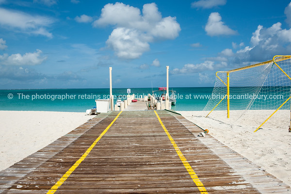 Walkway & jetty on beach, Caribbean white sand, turquoise sea, and blue sky. Providenciales, Turks & Caicos.<br /> Prints & downloads.