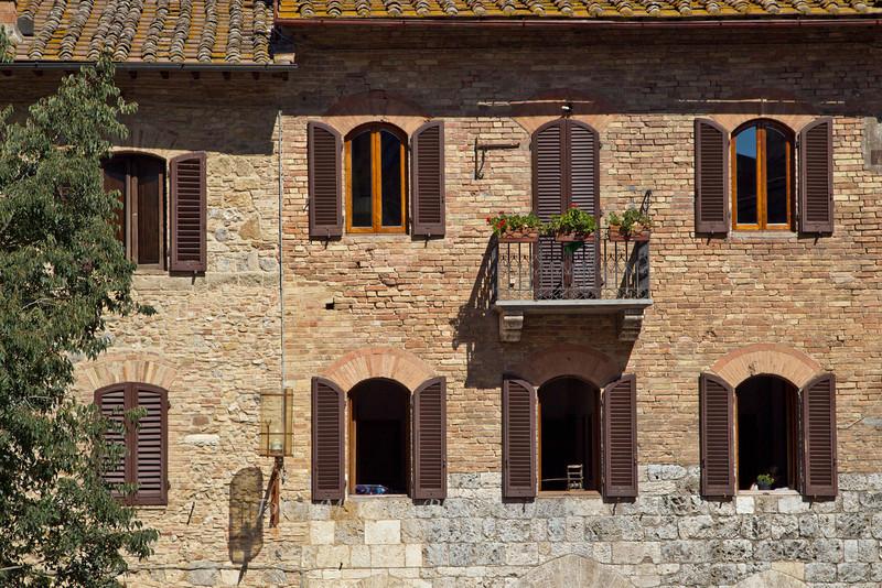Street scene, wall of windows, San Gimignano, Tuscany, Italy