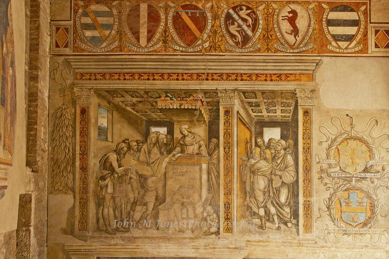 Old frescoes include coats of arms of city dignitaries, Piazza del Popolo, Palazzo del Popolo , San Gimignano, Tuscany, Italy