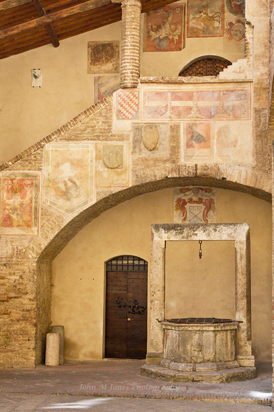 Piazza del Popolo with well and worn frescoes, Palazzo del Popolo, San Gimignano, Tuscany, Italy