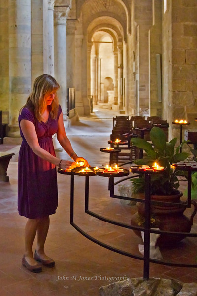 Woman lighting a candle, Sant' Antimo Abbey, near Siena, Tuscany, Italy