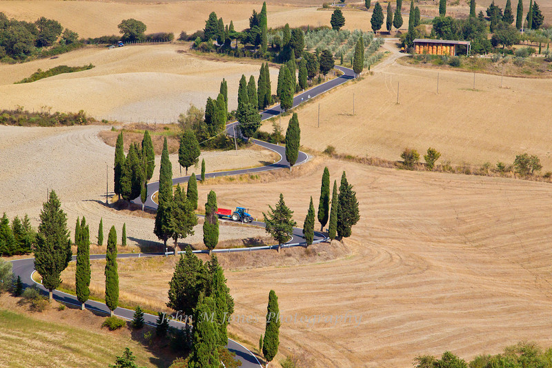 Tractor and trailer on a steep winding cypress-lined road through the farmland of Tuscany's Val d'Orcia, Siena, Italy