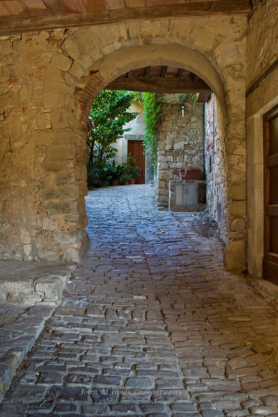 Narrow street and archway in Montefioralle, Tuscany, Italy