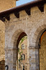 View through vaulted loggia, Piazza del Duomo, San Gimignano, Tuscany, Italy