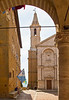 Cathedral of Pienza bell tower through arch of Palazzo Comunale, Siena, Tuscany, Italy